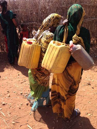También las niñas cargan los bidones con la cabeza
