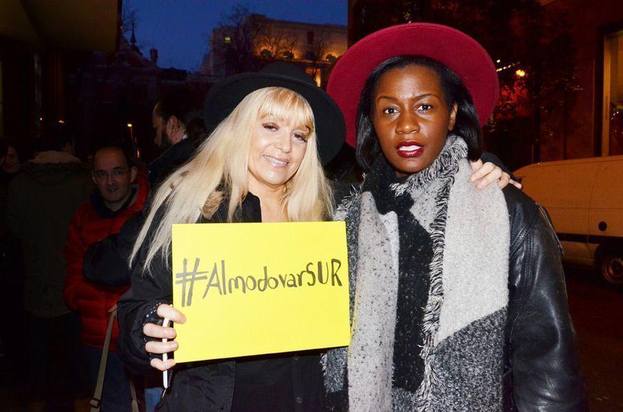 Dos fans con el cartel del hashtag del evento en Twitter difundido por la Escuela SUR. Foto: Víctor G. Carreño.