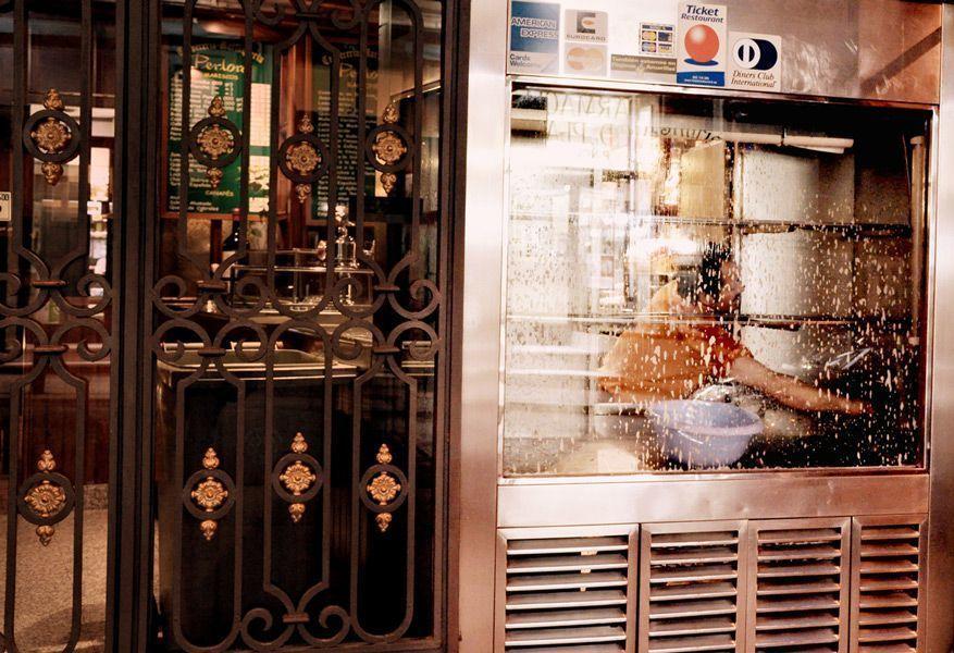 Camarero limpiando la vitrina de bodegones. Víctor G. Carreño