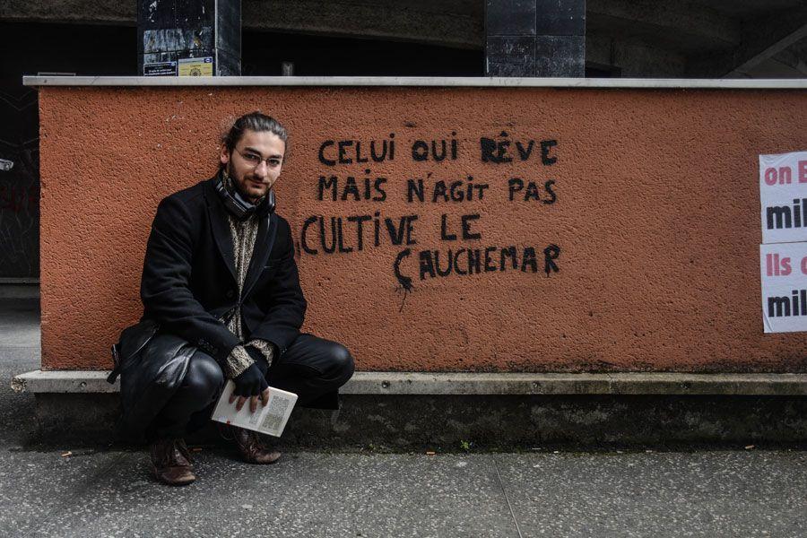 Marc Cohen posa delante de uno de los muros de la facultad: «Aquel que sueña pero no reacciona cultiva la pesadilla». Fotografía de Teresa Suárez.