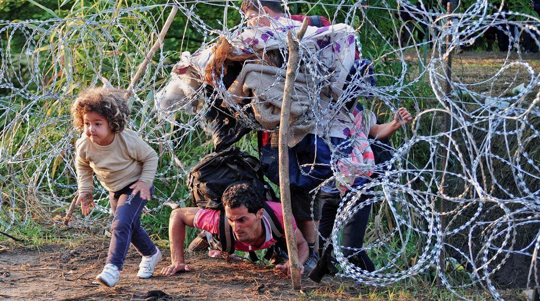 Familia trata de atravesar la valla fronteriza entre Hungría y Serbia. Foto: Csaba Segesvari
